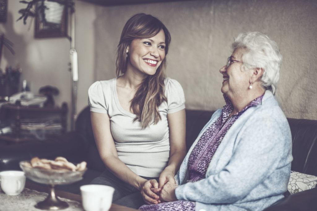 Nuori ja vanha nainen kahvittelemassa kotipalvelun aikana
