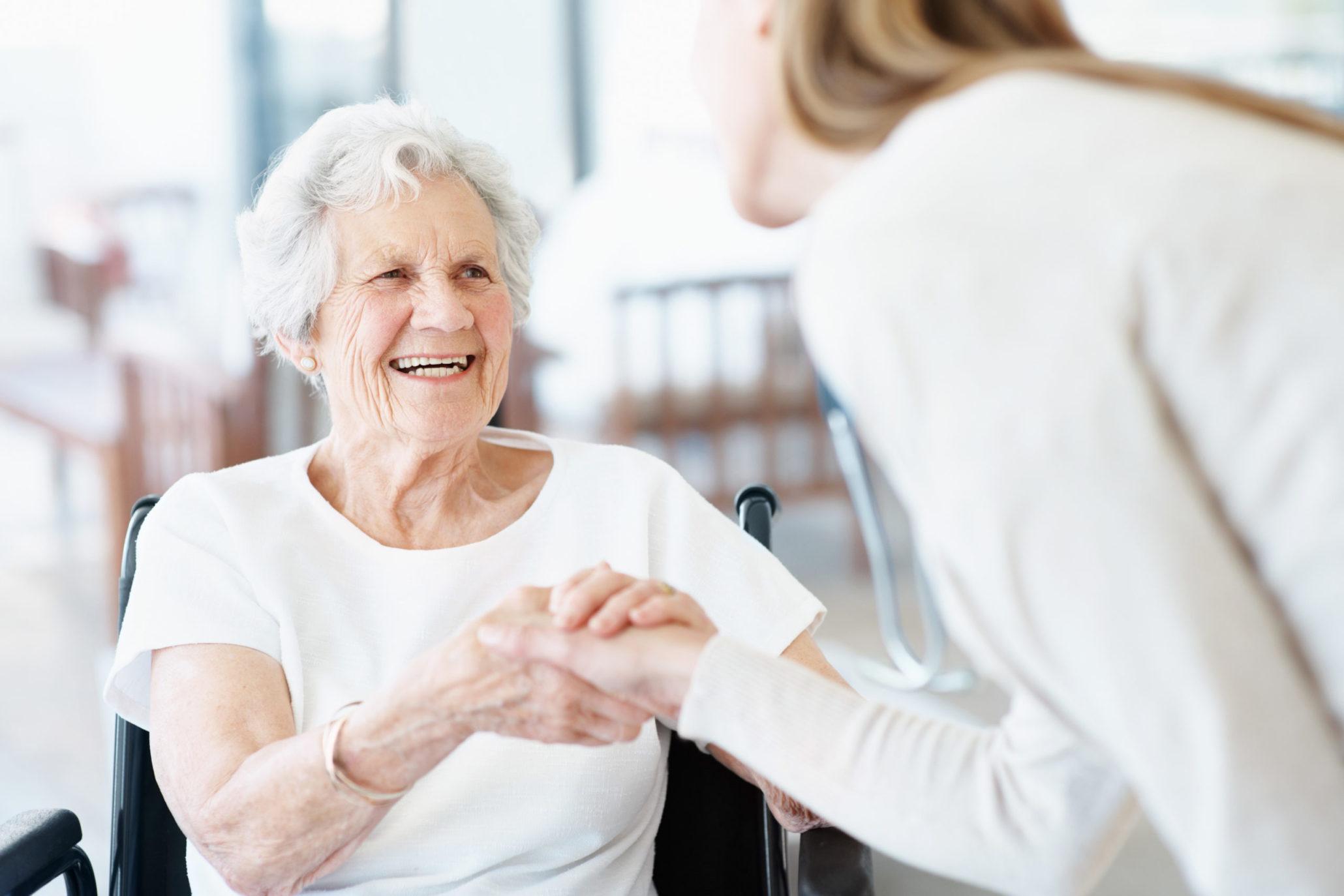 Nuori nainen hymyilee pyörätuolissa istuvalle ikäihmiselle