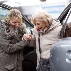 Nuori nainen auttaa vanhemman naisen ulos autosta
