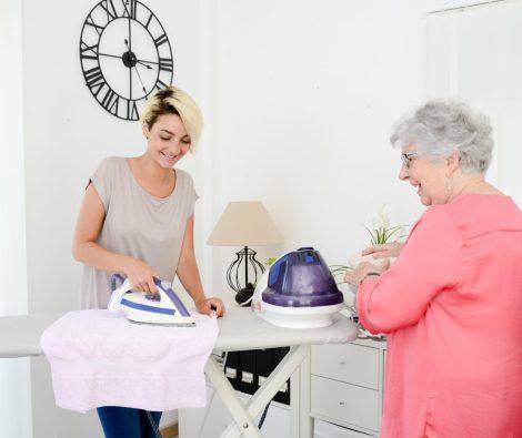 Nuori nainen silittää vanhemman naisen vaatteita seura- ja kotipalvelun aikana