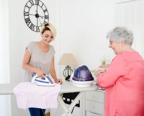 Nuori nainen silittää vanhemman naisen vaatteita