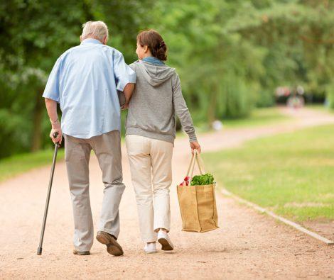 Nuorempi nainen antaa tukea iäkkäälle miehelle kävelyllä hoivapalvelun aikana