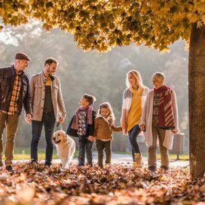 Kolme sukupolvea kävelemässä syksyisessä puistossa